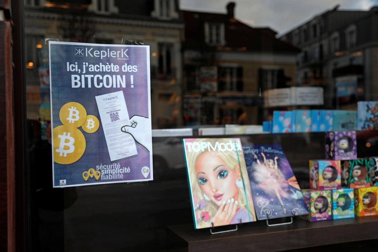 A placard of French startup Keplerk, for clients to purhcase bitcoins, is seen inside a tobacco shop at Rueil-Malmaison